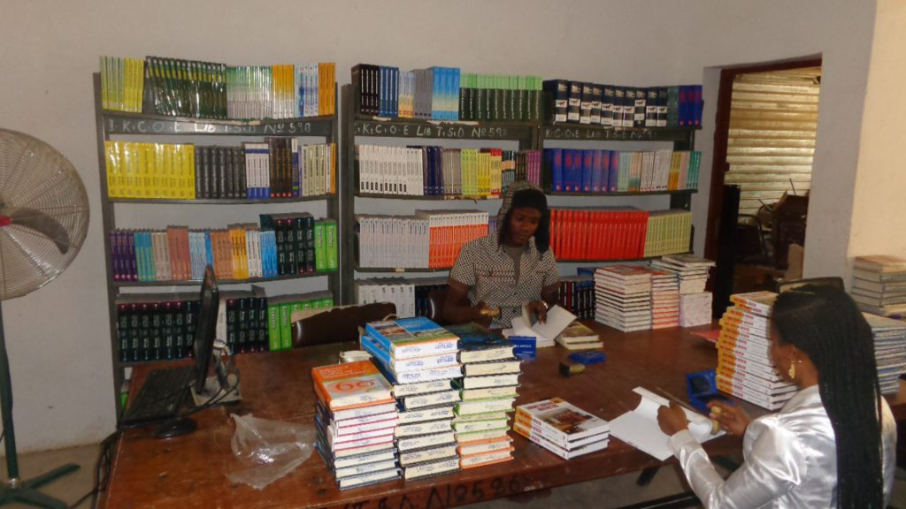 NEWLY SUPPLIED BOOKS BEING STAMPED IN COLLEGE LIBRARY